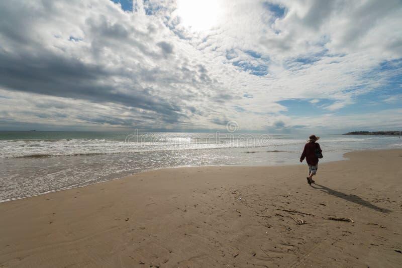 Oudere vrouw die op het strand lopen stock foto's