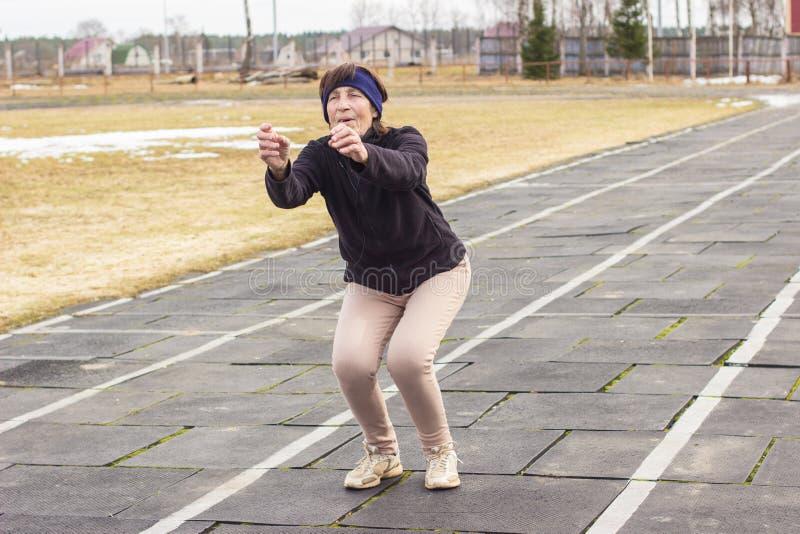 Oudere vrouw die openluchtoefening voor de benen doen stock afbeeldingen