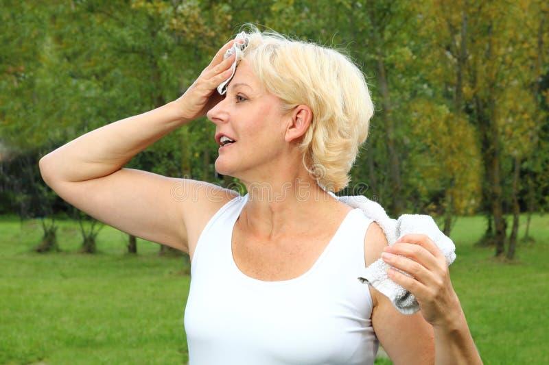 Oudere vrouw die sporten met handdoek doen royalty-vrije stock afbeelding