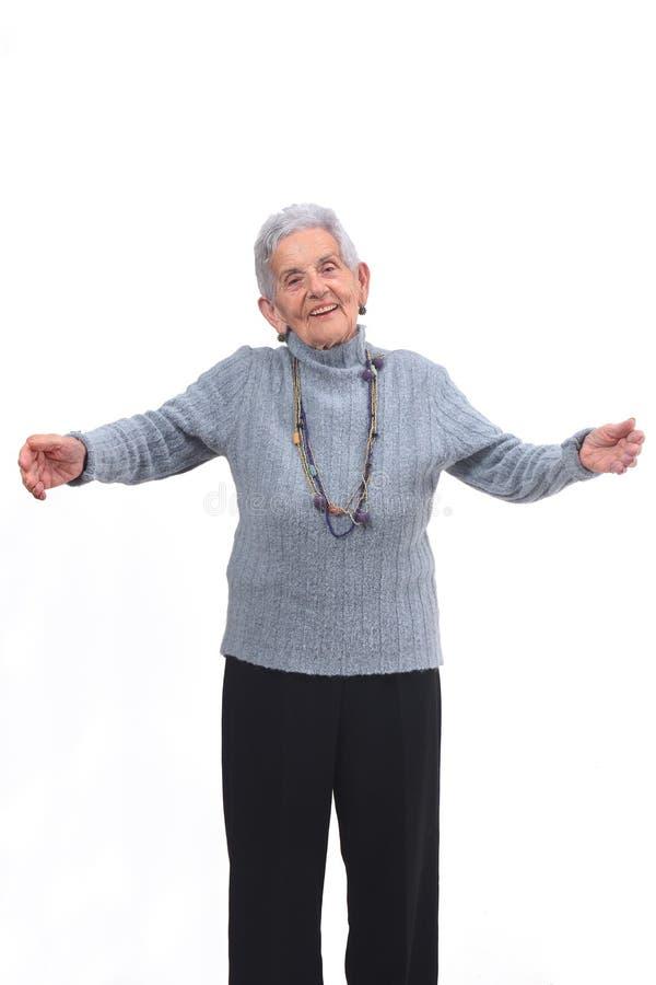 Oudere vrouw die u een omhelzing op witte achtergrond wil geven stock foto's