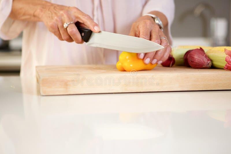 Oudere vrouw die verse groenten in keuken snijden stock afbeeldingen