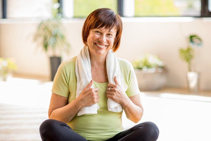 Oudere vrouw die yoga binnen doen royalty-vrije stock afbeeldingen
