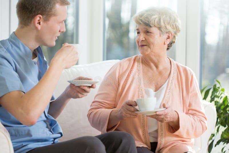 Oudere vrouw en verpleger stock afbeelding