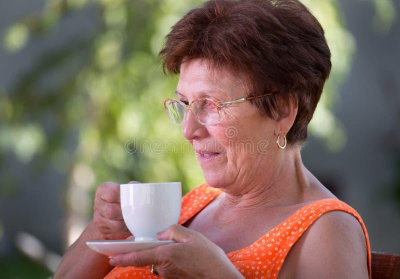 Oudere vrouw het drinken koffie stock afbeeldingen
