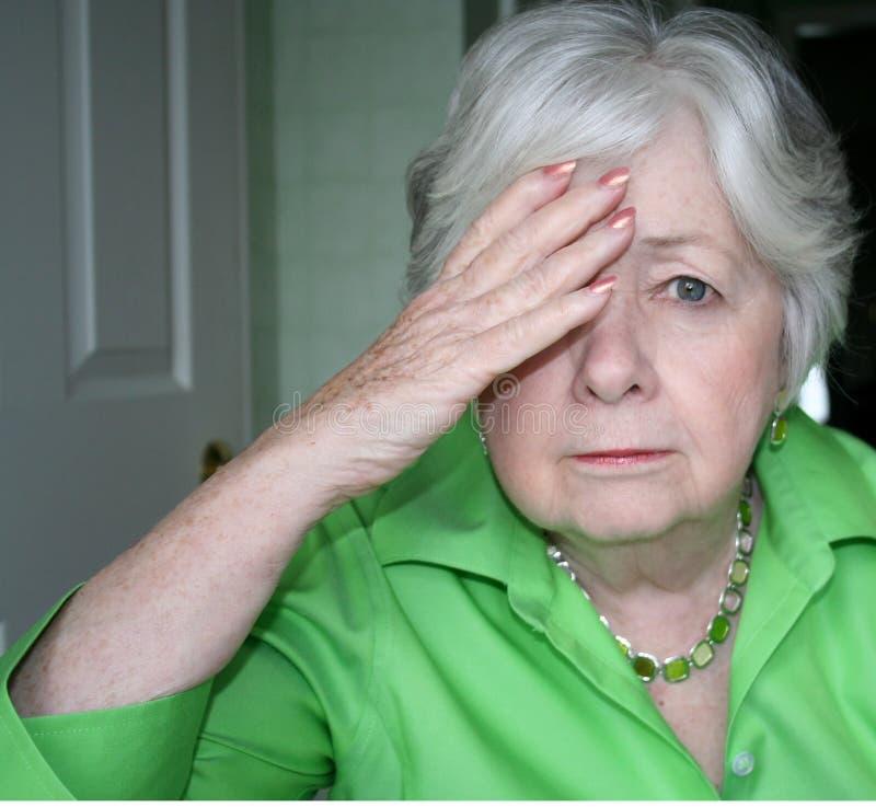 Oudere Vrouw met Één Hand aan Hoofd royalty-vrije stock afbeelding