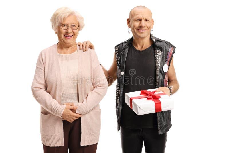 Oudere vrouw met een punkman die een cadeau vasthoudt en glimlacht stock foto