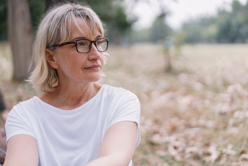 Oudere vrouwen dragen een caucasiaanse bril terwijl ze in het najaar in het openbare park zitten te denken stock foto
