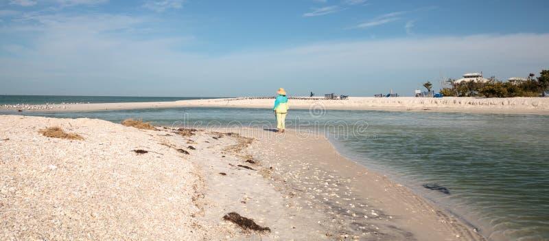 Oudere vrouwentribunes op het witte zandstrand voor aquablauw stock fotografie