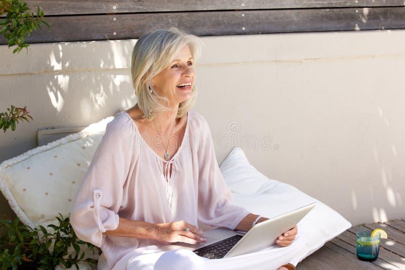 Oudere vrouwenzitting buiten het werken aan laptop royalty-vrije stock foto's