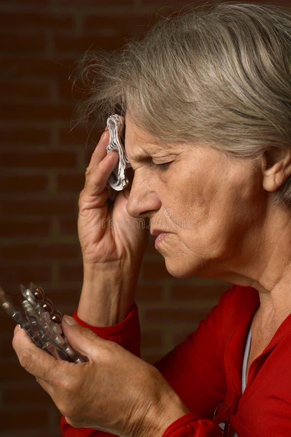 Oudere zieke vrouw in rood royalty-vrije stock foto's