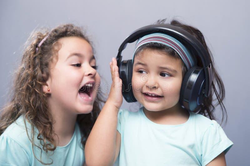 Oudere zuster die bij haar jongere zuster in hoofdtelefoons gillen royalty-vrije stock afbeelding