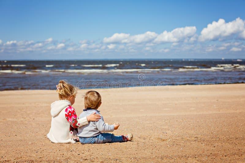 Oudere zuster en jongere broerzitting in sweaters op beac royalty-vrije stock afbeeldingen