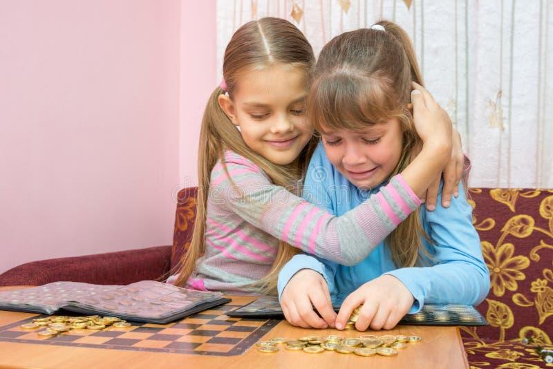Oudere zuster troostende schreeuwende jongere zuster, wat een stapel muntstukken verzamelt stock foto