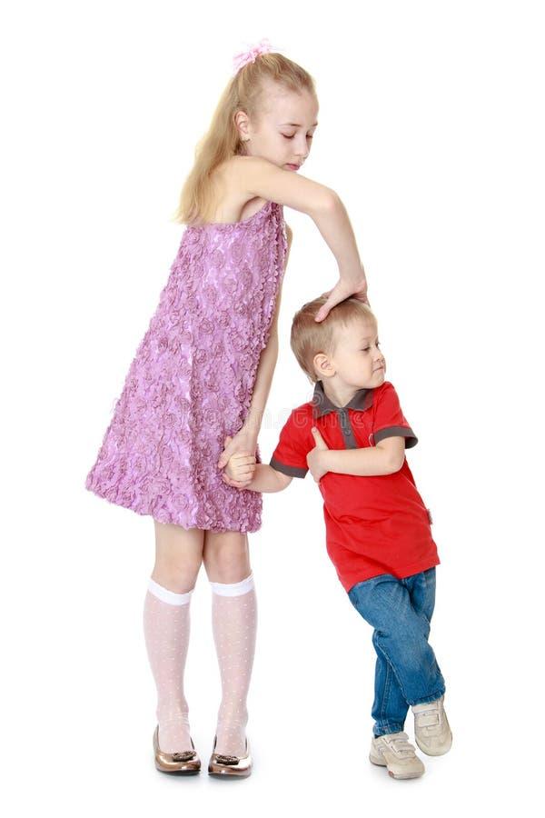 Oudere zusterspelen met weinig broer stock foto