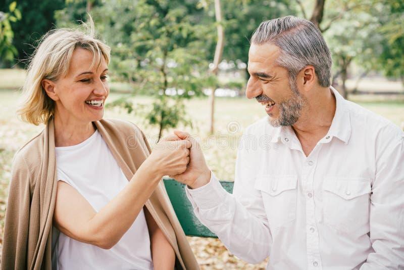 Ouderen die op een bank zitten en elkaar plezier beleven en gelukkig lachen in het openbare park 's ochtends royalty-vrije stock fotografie