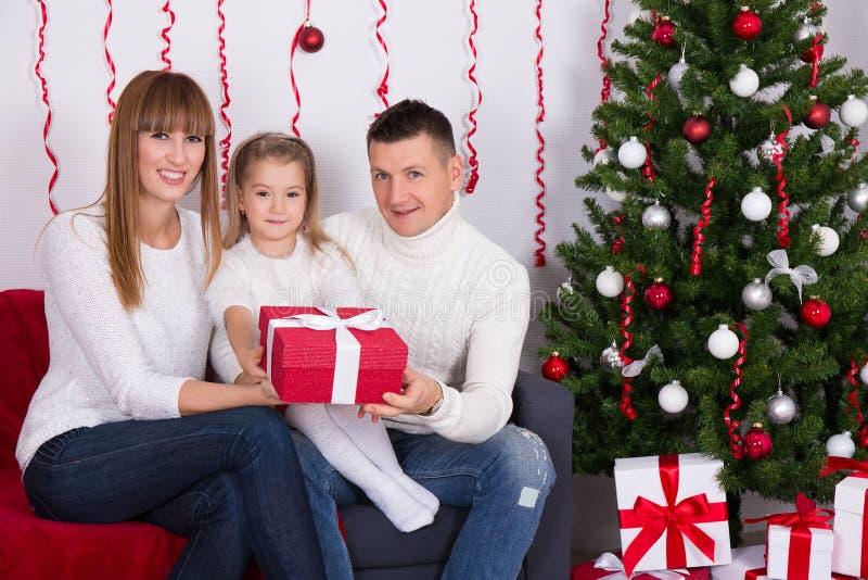 Ouders aanwezige geven aan dochter voor Kerstboom stock afbeelding