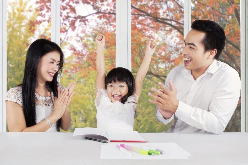 Ouders die applaus op hun dochter geven stock fotografie