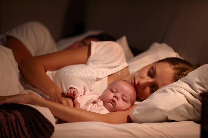 Ouders die in Bed met Pasgeboren Baby slapen stock afbeeldingen