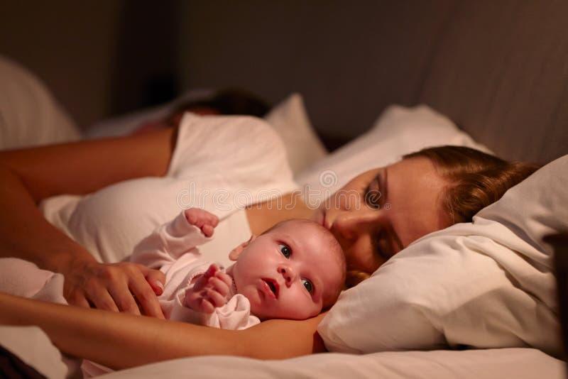 Ouders die in Bed met Pasgeboren Baby slapen stock foto