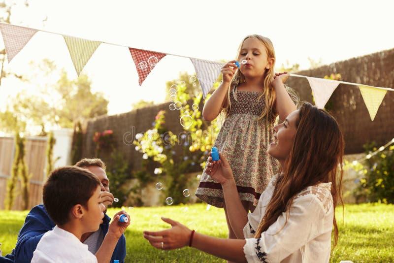 Ouders die Bellen met Kinderen in Tuin blazen stock afbeeldingen