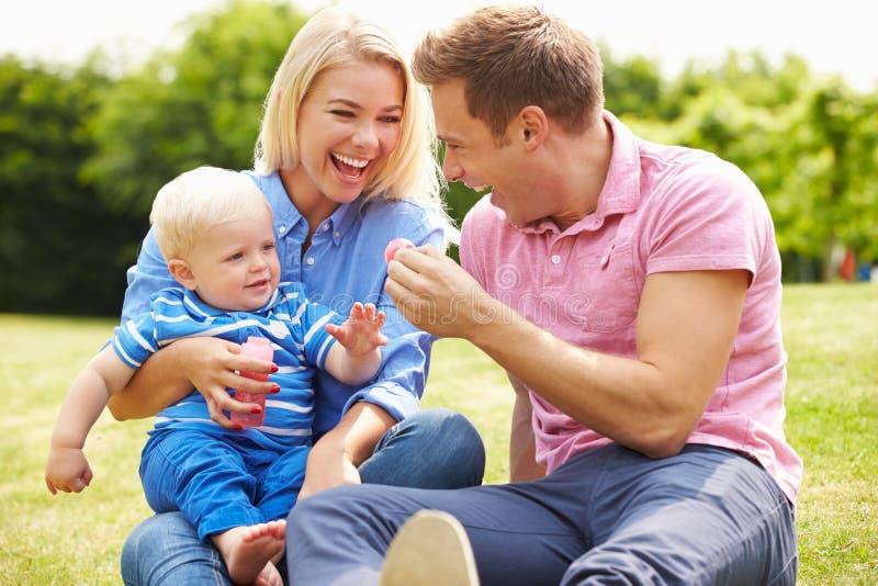 Ouders die Bellen voor Jonge Jongen in Tuin blazen stock afbeelding