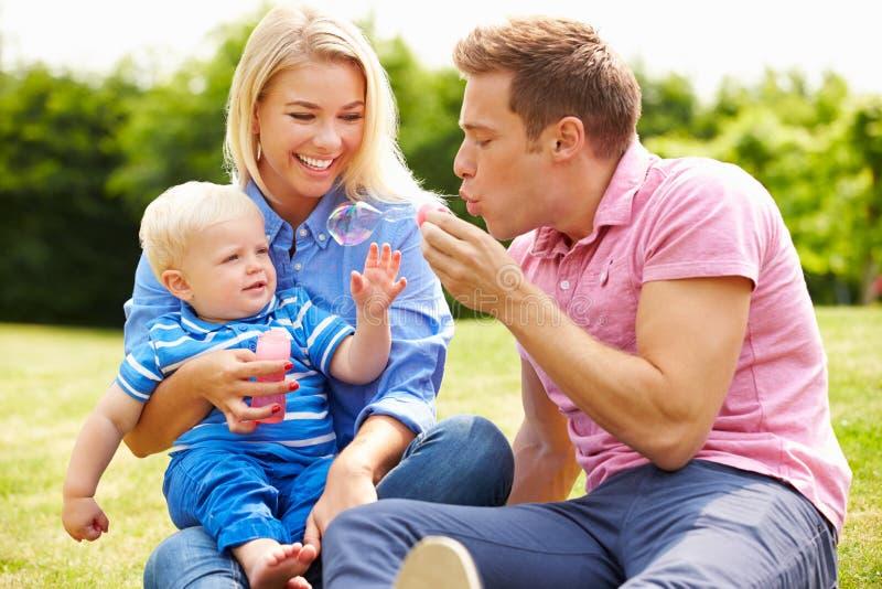 Ouders die Bellen voor Jonge Jongen in Tuin blazen royalty-vrije stock foto