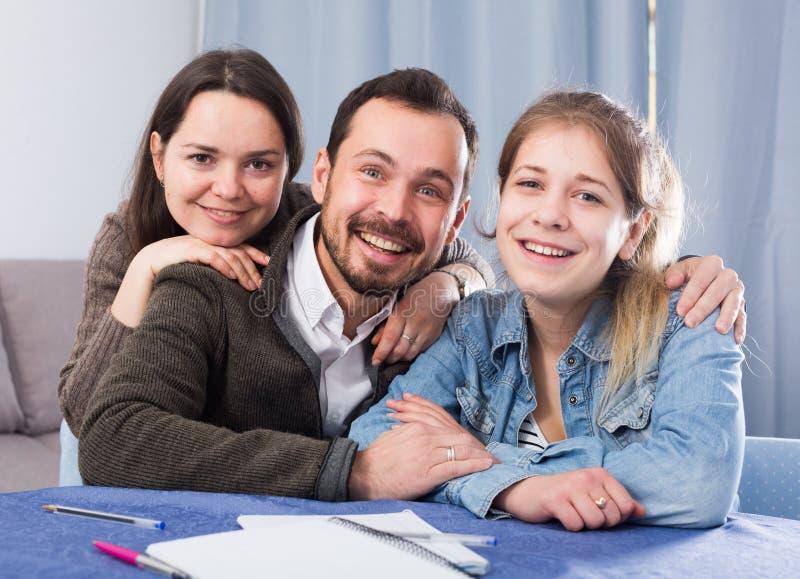 Ouders die dochter met thuiswerk helpen stock foto