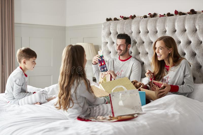 Ouders die Giften van Kinderen openen aangezien zij Sit On Bed Exchanging Present op Kerstmisdag royalty-vrije stock foto's