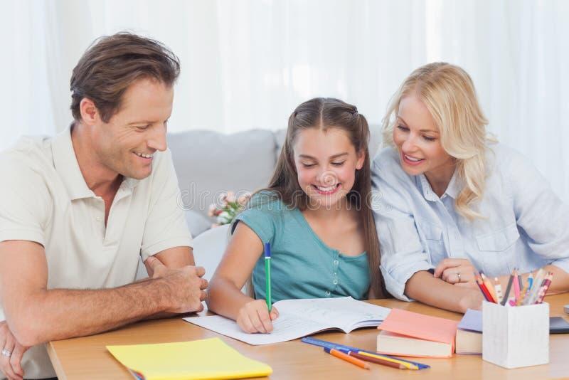 Ouders die haar dochter helpen die haar thuiswerk doen royalty-vrije stock foto's