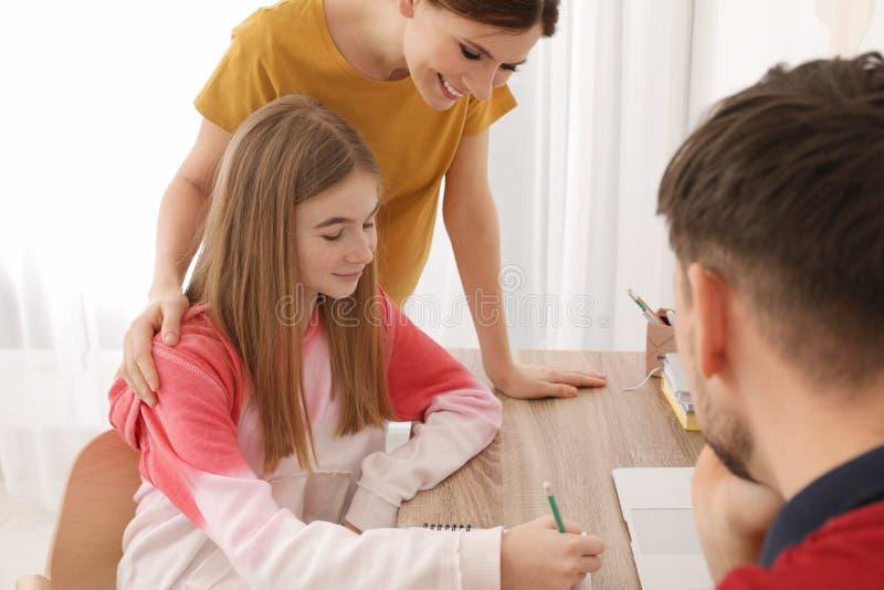 Ouders die hun tienerdochter met thuiswerk helpen stock foto