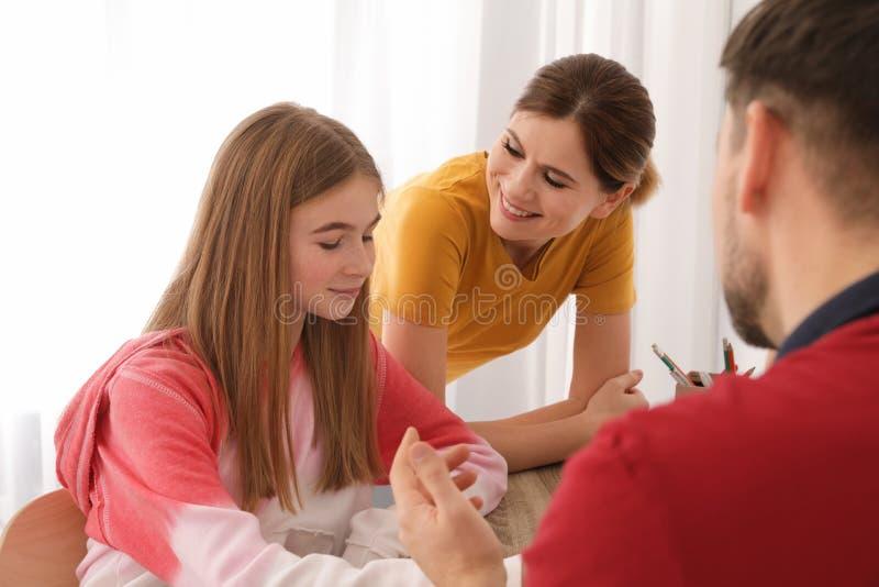 Ouders die hun tienerdochter met thuiswerk helpen stock afbeelding