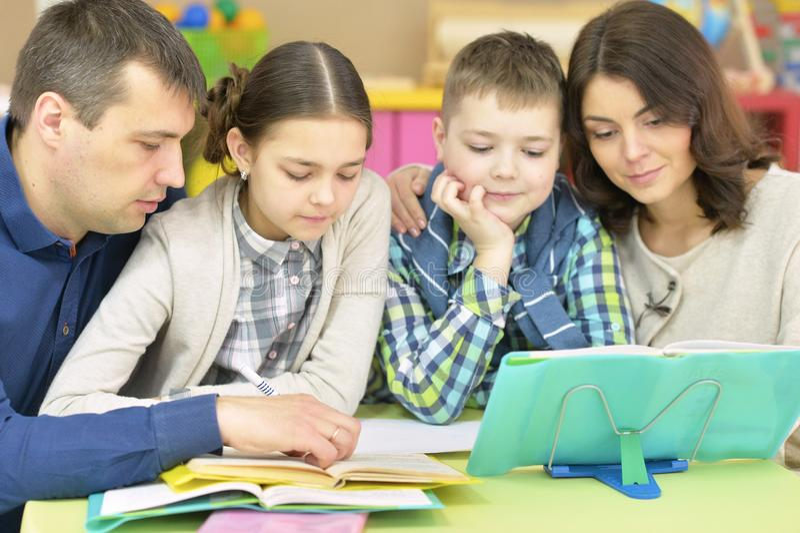 Ouders die kinderen met thuiswerk helpen royalty-vrije stock afbeeldingen