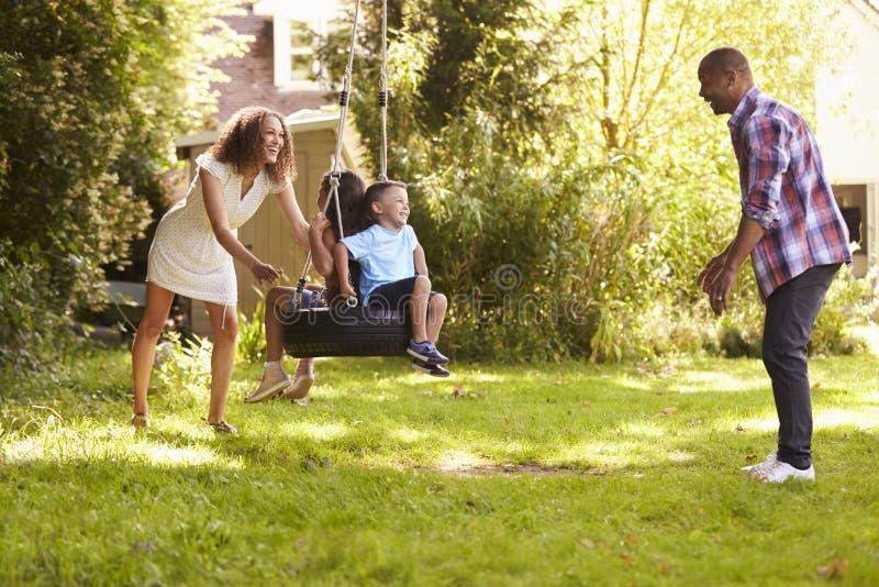 Ouders die Kinderen op Bandschommeling duwen in Tuin stock afbeeldingen