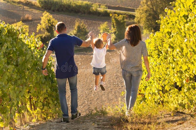 Ouders die klein meisje opheffen door wapens in wijngaard, achtermening royalty-vrije stock foto's