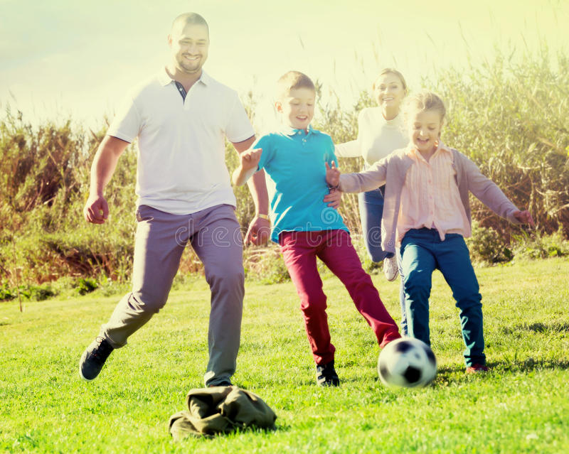 Ouders die met twee jonge geitjes voetbal spelen stock foto's