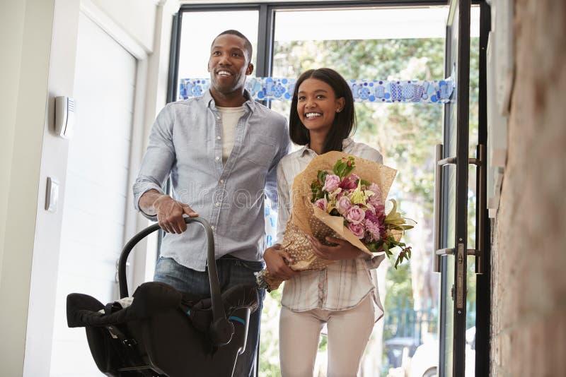 Ouders die naar huis met Pasgeboren Baby in Auto Seat aankomen stock foto's