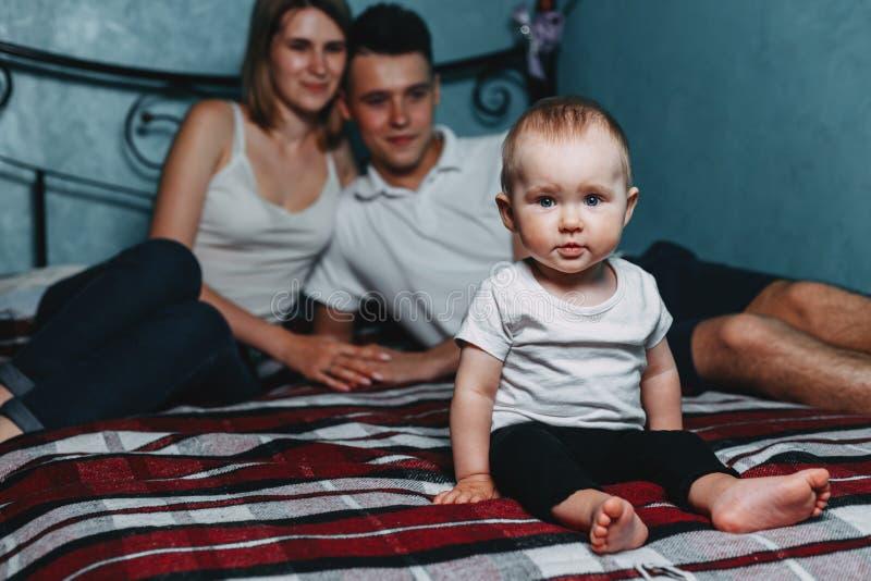 Ouders die op bed zitten die thuis op dochter letten royalty-vrije stock afbeelding