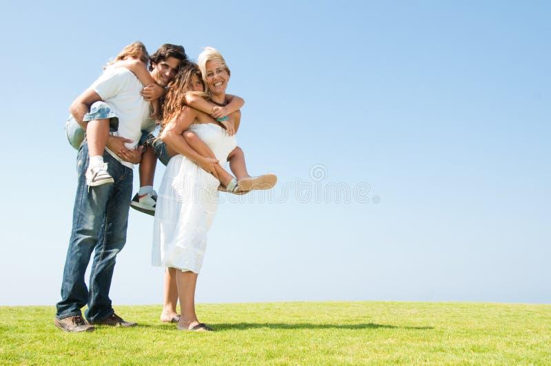 Ouders die op de rug ritten geven stock afbeeldingen