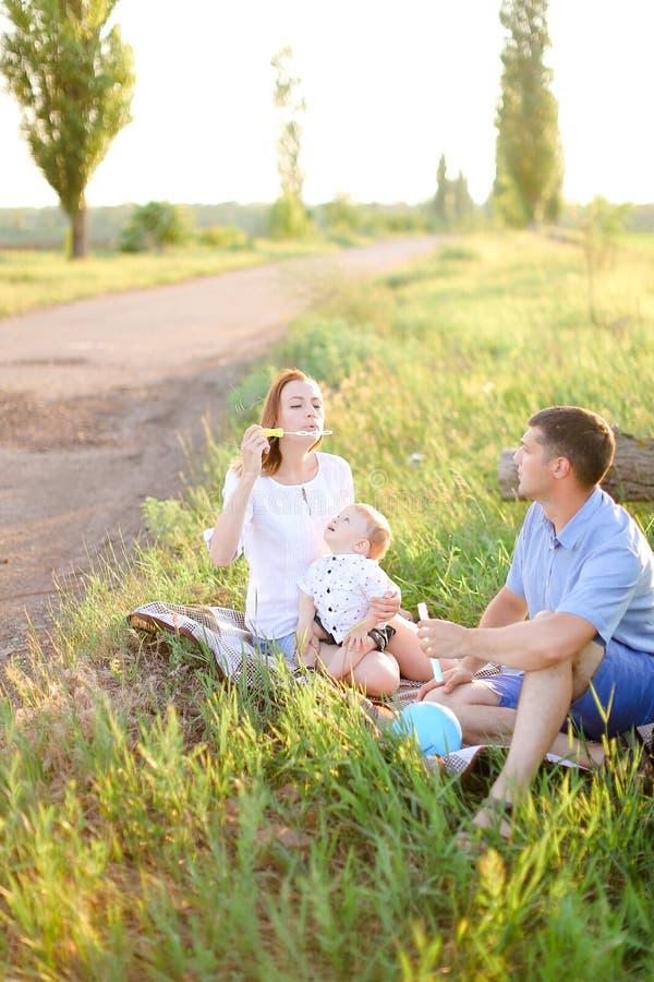 Ouders die op gras met weinig kind en blazende bellen zitten stock afbeeldingen