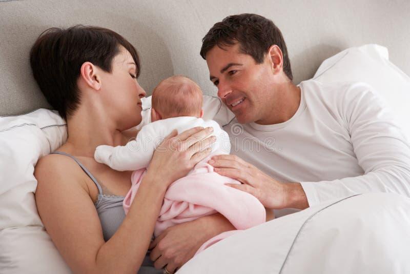 Ouders die Pasgeboren Baby in Bed knuffelen royalty-vrije stock afbeeldingen