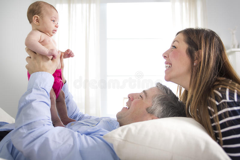 Ouders die Pasgeboren Baby in Bed thuis knuffelen stock afbeeldingen