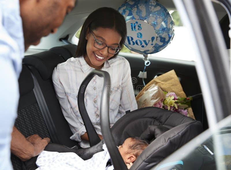 Ouders die Pasgeboren Babyhuis in Auto brengen stock afbeelding