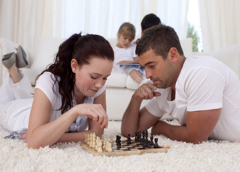 Ouders die schaak op vloer in woonkamer spelen royalty-vrije stock afbeeldingen