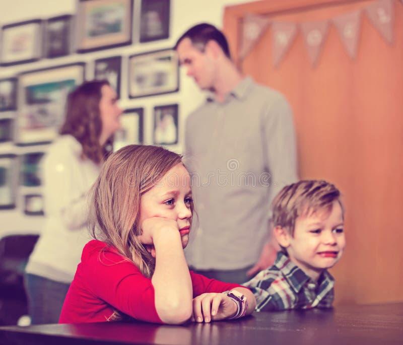 Ouders die slechte rij hebben terwijl hun kinderen thuis royalty-vrije stock afbeelding