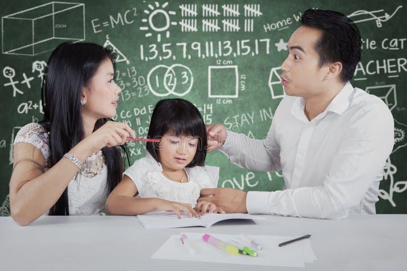 Ouders die terwijl het onderwijzen van hun kind debatteren royalty-vrije stock afbeeldingen