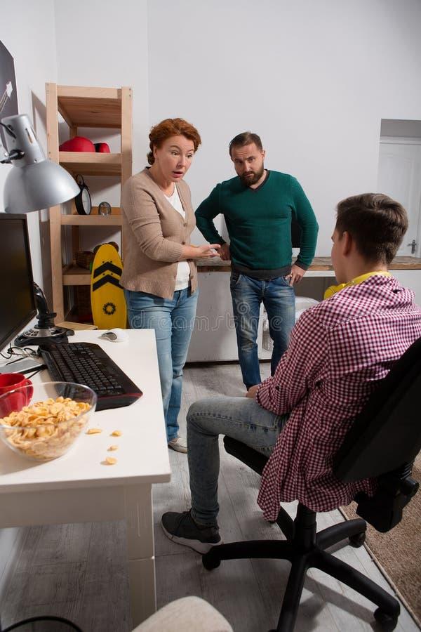 Ouders die tiener verklaren hoe hamfurl het computerspel is stock foto's