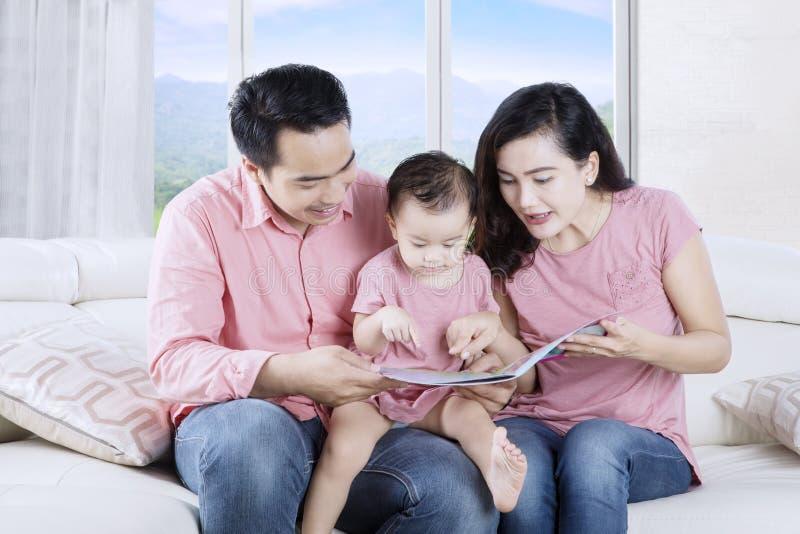 Ouders die verhaal lezen aan kind stock foto's