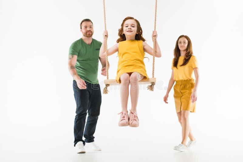 Ouders die weinig gelukkige dochter berijden op schommeling royalty-vrije stock fotografie