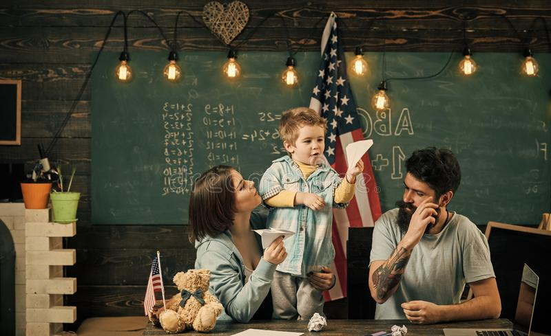 Ouders die zoon het Amerikaanse tradities spelen onderwijzen Jong geitje met ouders in klaslokaal met de vlag van de V.S., bord o stock afbeelding
