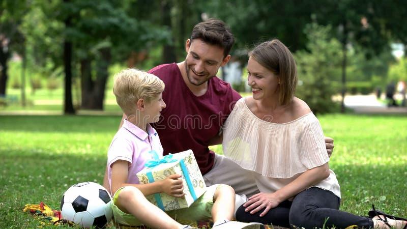 Ouders die zoon met verjaardag gelukwensen, die huidige doos, gelukkige familie geven royalty-vrije stock afbeeldingen